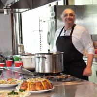 Syrian refugee chef Nazem Jamal Alddin serves his home country's food from the kitchen at a pop-up restaurant in Tokyo's Minato Ward on Sept. 5. | CHISATO TANAKA