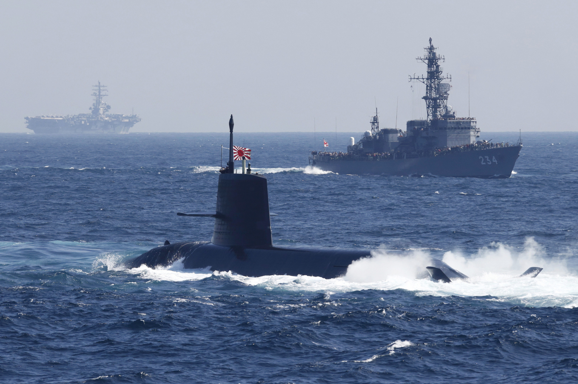 The Maritime Self-Defense Force submarine Kokuryu, displaying the Rising Sun flag, sails past a vessel during a fleet review in Sagami Bay, off Yokosuka, Kanagawa Prefecture, in October 2015. | BLOOMBERG