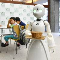 An OriHime-D robot, operated remotely by a severely disabled person at their home, serves customers at a cafe set up in Tokyo on a trial basis in August. | KYODO