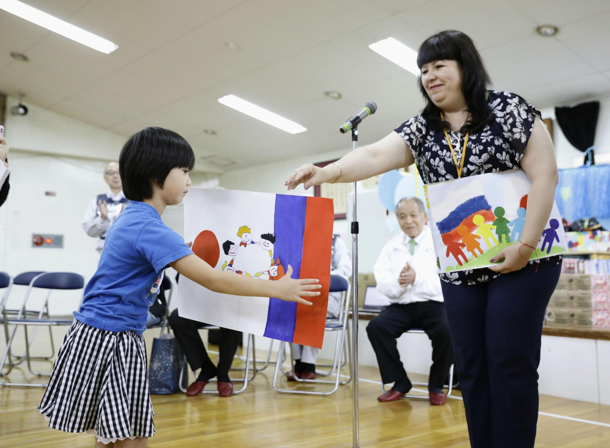 A Russian woman presents paintings made by Russian children at a nursery school in Mukawa, Hokkaido, on Saturday. | KYODO