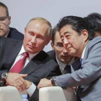 Russian President Vladimir Putin and Prime Minister Shinzo Abe attend an international judo tournament on the sidelines of the Eastern Economic Forum in Vladivostok, Russia, on Wednesday. | REUTERS