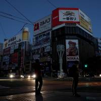 Neon lights above Sapporo's famed nightlife district darkened by quake