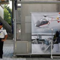 A Ground Self-Defense Force's recruiter stands in front of a promotional booth during a public relations event to attract recruits in Tachikawa, western Tokyo, on Aug. 26. | REUTERS