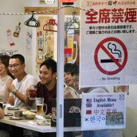 People drink and dine at a restaurant with a nonsmoking sign in Tokyo's Chiyoda Ward in July. | KYODO