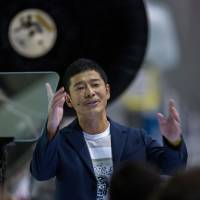 Yusaku Maezawa speaks near a Falcon 9 rocket during an announcement naming him as the first private passenger who will fly around the moon aboard the SpaceX BFR launch vehicle, at the SpaceX headquarters and rocket factory in Hawthorne, California, on Monday. | AFP-JIJI