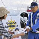 A Kanagawa Prefectural Expressway Traffic Police Unit official hands out leaflets calling for the abolishment of tailgating at the Tomei Expressway's Ebina service area on June 1.