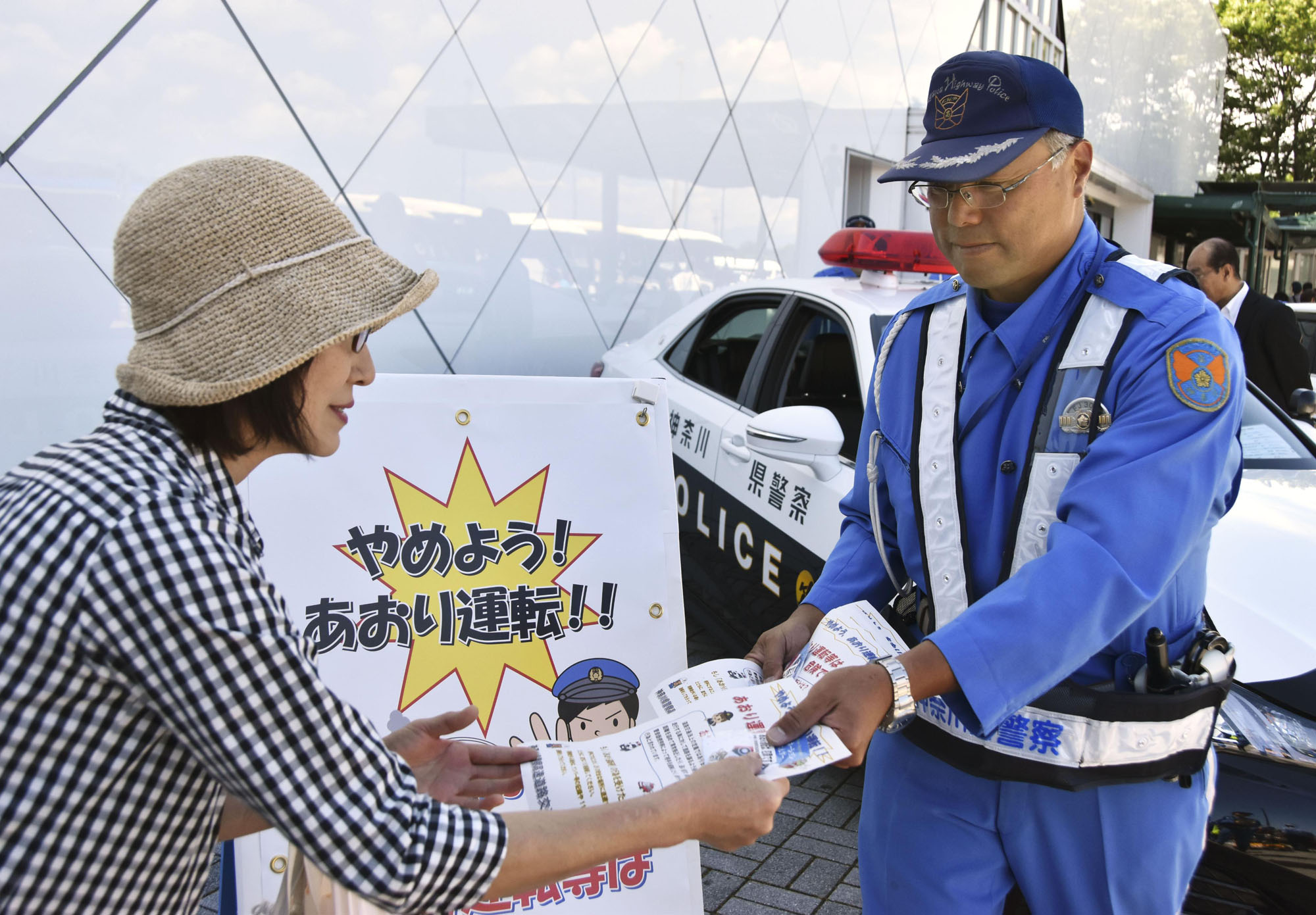 A Kanagawa Prefectural Expressway Traffic Police Unit official hands out leaflets calling for the abolishment of tailgating at the Tomei Expressway