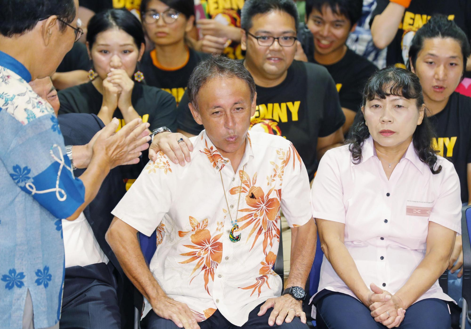 Denny Tamaki, center, the winner of the Okinawa gubernatorial race, watches the results on TV on Sunday in Naha. | KYODO