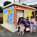 Local children pose in front of a public lavatory that they helped paint in Asahi Park in Tokyo's Sugamo district on Sunday.