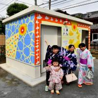 Local children pose in front of a public lavatory that they helped paint in Asahi Park in Tokyo's Sugamo district on Sunday. | YOSHIAKI MIURA