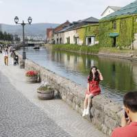 Tourists take a photo at the Otaru Canal, a tourist spot in the port city of Otaru in western Hokkaido. Government data released Wednesday shows growth in the number of foreign tourists coming to Japan has slowed due to recent disasters in the country as well as scorching summer heat. | KYODO