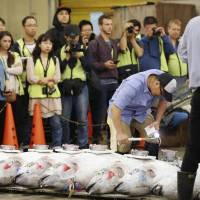 Media crews watch a tuna auction at Tsukiji market on Friday. Saturday will be the last day for the public to visit the market at its current site before the facility is relocated next month. | POOL / VIA KYODO