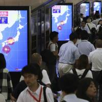 Monitors show the projected course of Typhoon Jebi at JR Osaka Station Monday night. Some train services in western Japan were suspended Tuesday as the powerful typhoon is on course to hit the region. | KYODO