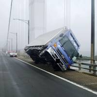 Strong winds from Typhoon Jebi blew this truck over as it crossed the Seto Ohashi Bridge in Sakaide, Kagawa Prefecture, on Tuesday. | KAGAWA PREFECTURAL POLICE / VIA KYODO