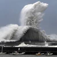High waves break over a concrete wall at a fishing port in Aki, Kochi Prefecture, on Tuesday as Typhoon Jebi approached western Japan. | KYODO