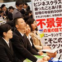 University students listen to a company presentation at a job fair at Makuhari Messe convention center in the city of Chiba in March 2017. A new survey has revealed that young Japanese in their 20s don't want to live into their 80s, with their top concern being economic worries in old age. | BLOOMBERG