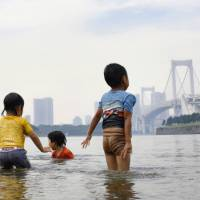 Testing the water: Children play in the ocean at Odaiba Beach in July 2017. | KYODO