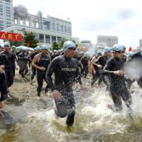 Participants take part in a swimming event to promote the Tokyo 2020 Olympics at Odaiba Beach in August 2013. | KYODO