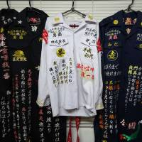 Image problem: A collection of tokkōfuku uniforms embroidered by garment maker Kazuhiro Nakagawachi hangs on a wall in his prefabricated office in Kyoto in August.   TOMOHIRO OSAKI