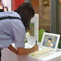Saying farewell: A woman signs a book at Chibi Maruko-chan Land, a museum dedicated to the manga series of the same name. | KYODO
