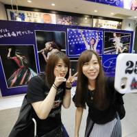 End of an era: Fans take a selfie in front of a display advertising Namie Amuro's recent best-of album. | KYODO