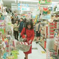 Treasure hunt: A shopper fills her basket in a Don Quijote outlet in Tokyo's Shinjuku district.   BLOOMBERG