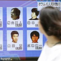 Little sympathy: A woman walks past a television screen in Tokyo showing four former Aum Shinrikyo cult members who were executed in July. The executions of 13 Aum cultists in July aroused little domestic outrage. | KYODO