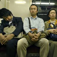 Paying down sleep debt: Passengers doze off while riding on a train in Tokyo. | GETTY IMAGES