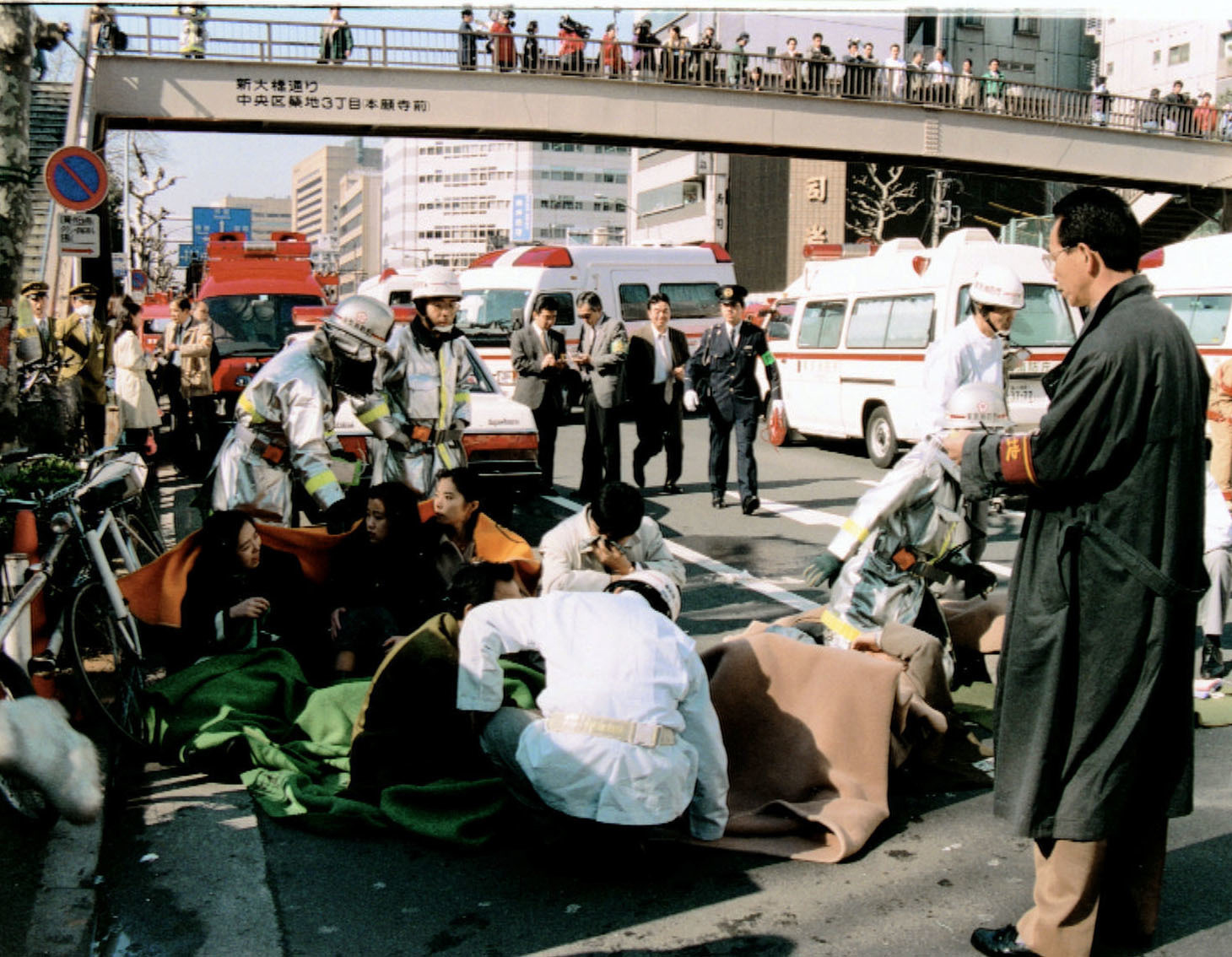 Victims of the Aum sarin attacks receive treatment in front of Tsukiji Station in Tokyo, March 20, 1995. | KYODO