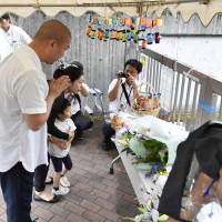 People lay flowers and pray in front of Tsukui Yamayuri En in Sagamihara, Kanagawa Prefecture, on Wednesday, the first anniversary of a vicious attack in which 19 people were fatally stabbed and 26 injured.   KYODO