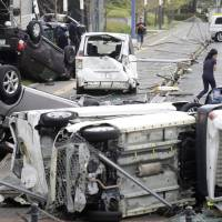 Nature's toll: Cars lie damaged in Osaka on Sept. 4 after powerful Typhoon Jebi passed through western Japan. In addition, this summer saw flooding in southwestern Japan, a record-breaking heat wave and the Sept. 6 Hokkaido earthquake. | KYODO