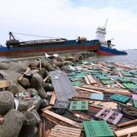 Two ships sit grounded on a breakwater strewn with debris at Amagasakinishinomiya Port in Hyogo Prefecture on Sept. 6 in the wake of Typhoon Jebi. | BLOOMBERG