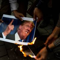 Iranians burn a photo of U.S. President Donald Trump during a protest in Tehran.   BLOOMBERG