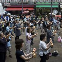 People exercise on Respect for the Aged Day at a temple in the Sugamo neighborhood in Toshima Ward, Tokyo, in September 2016. The proportion of Japan's aged has been rising steadily for decades. | BLOOMBERG