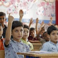 Palestinian students attend a lesson at a school operated by United Nations Relief and Works Agency in the Al-Baqaa Palestinian refugee camp in Jordan last Thursday. The United States, by far the biggest contributor to the agency, announced it was halting its funding for the organization, which it labelled 'irredeemably flawed.' | AFP-JIJI