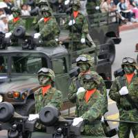 Taiwanese military vehicles roll through Taipei during a National Day parade carrying U.S.-made Javelin anti-tank missiles. | BLOOMBERG NEWS