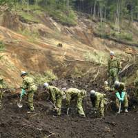 Self-Defense Forces personnel work at the site of a landslide in Atsuma, Hokkaido, on Sunday after a strong earthquake struck the country's northernmost island Thursday morning. | KYODO
