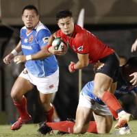 Canon's Yu Tamura carries the ball against Toshiba in the teams' Top League opener on Friday night at Prince Chichibu Memorial Rugby Ground. The Eagles defeated the Brave Lupus 26-20. | KYODO