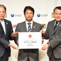 Japan Esports Union chairman Hideki Okamura (left), Ibaraki Prefecture Gov. Kazuhiko Oikawa (center) and Japan Football Association chairman Kozo Tashima pose for photos at a news conference promoting the Inter Prefectural eSports Championship on Tuesday. | DAN ORLOWITZ