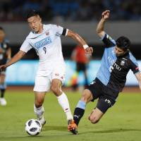 Consadole's Ken Tokura (left) and Fontale's Yusuke Tasaka vie for the ball during the match on Saturday. | KYODO