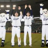 Seibu Lions first baseman Hotaka Yamakawa (center left) and pitcher Tatsuya Imai (center right) celebrate Sunday's win over the SoftBank Hawks with mascots Raina (left) and Leo at MetLife Dome in Tokorozawa, Saitama Prefecture. | KYODO