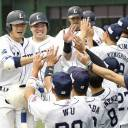The Lions' Takumi Kuriyama (left) returns to the dugout after hitting a grand slam during the first inning of Seibu's 8-1 win over the Hawks on Monday at MetLife Dome.