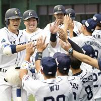 The Lions' Takumi Kuriyama (left) returns to the dugout after hitting a grand slam during the first inning of Seibu's 8-1 win over the Hawks on Monday at MetLife Dome. | KYODO
