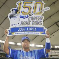 The BayStars' Jose Lopez holds up a commemorative board after hitting the 150th home run of his NPB career during his team's 6-1 victory over the Giants on Wednesday night at Tokyo Dome. | KYODO