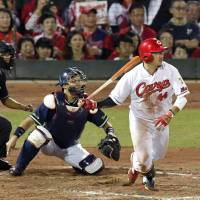 The Carp's Ryuhei Matsuyama drives in a run with a double during the first inning against the Swallows on Wednesday at Mazda Stadium in Hiroshima.   KYODO
