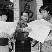 Takanohana (right), then called Takahanada, reads the newly-released sumo rankings, in which he and elder brother Wakanohana (left), then called Wakahanada are listed for the first time, with their father and stablemaster Fujishima standing between them in April, 1988. | KYODO