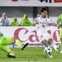 Frontale's Akihiro Ienaga (center) takes a shot during the first half against Bellmare on Wednesday in Hiratsuka, Kanagawa Prefecture. | KYODO
