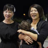 Mieko Saito (left), the widow of deceased judoka Hitoshi Saito, and Ayumi Tanimoto arrive at the Judo Federation Hall of Fame induction ceremony in Baku on Tuesday night. | KYODO