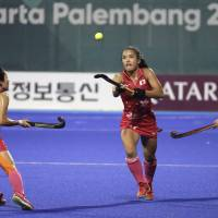 Motomi Kawamura (center) moves for the ball in the women's field hockey final against India at the Asian Games on Friday night. | AP