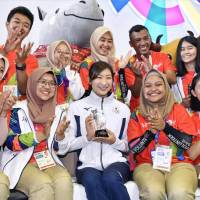 Swimmer Rikako Ikee (center)  sits with volunteers as she holds her trophy after being named Asian Games MVP on Sunday in Jakarta. | KYODO